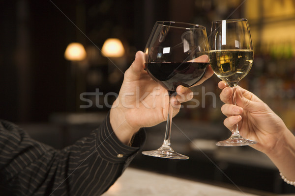 Stock photo: Hands toasting wine.