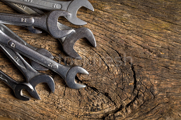 chrome spanners on old wooden table background