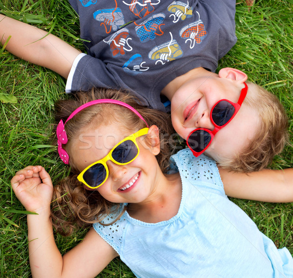 Stock photo: Picture presenting kids relaxinng on the grass