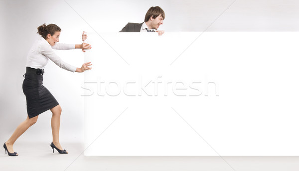 Stock photo: Business people pulling big white board, lots of copyspace