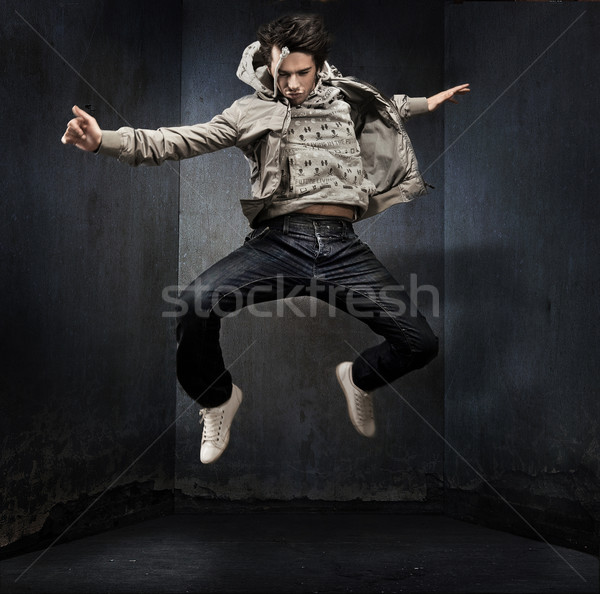 Stock photo: Young hip-hop dancer over a grunge wall