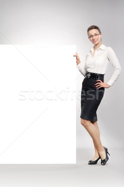 Stock photo: Attractive businesswoman showing empty white board