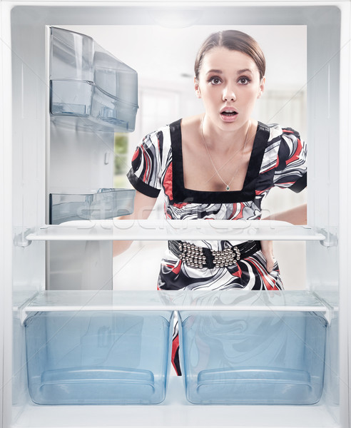 Stock photo: Young woman looking on empty shelf in fridge.