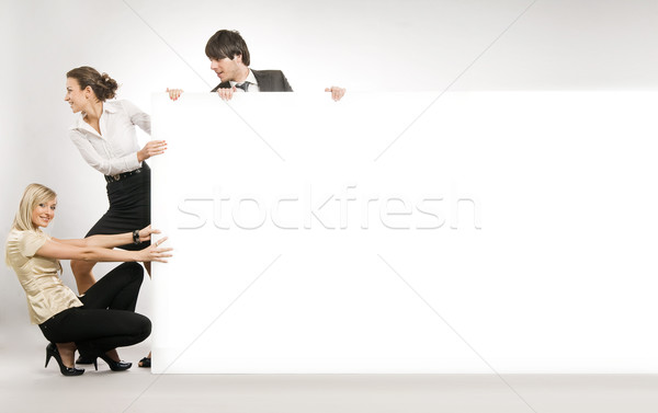 Stock photo: Business people pushing big white board, lots of copyspace