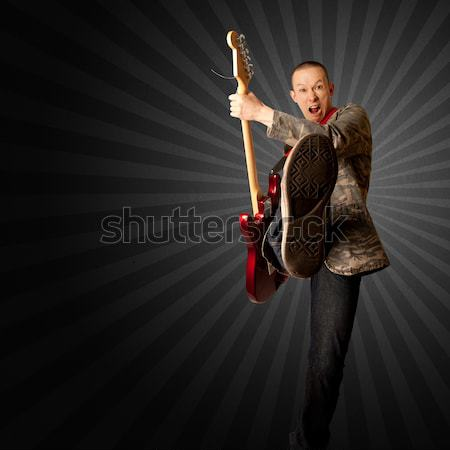 Stock photo: rocker with guitar and foot