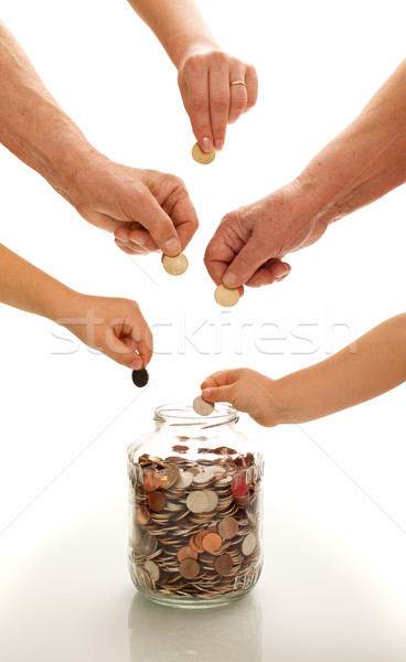 Stock photo: Hands of different generations saving coins