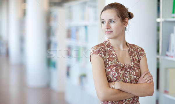 Stock photo: pretty young college student in a library (shallow DOF; color to