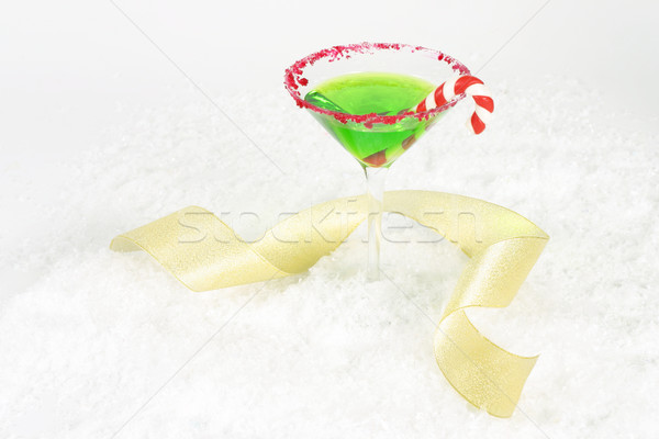 Christmas martini and gold curling ribbon on a snow white background. Space for copy.