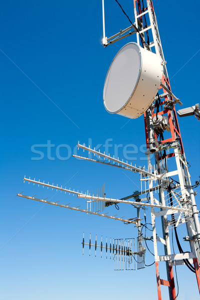 Stock photo: Antenna repeater messy mast in blue sky
