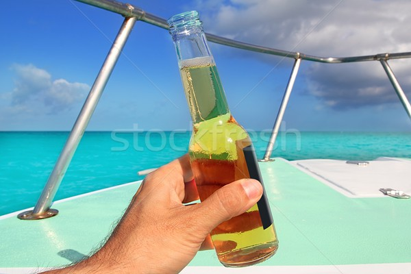 beer on hand Caribbean in boat bow turquoise sea enjoying vacation