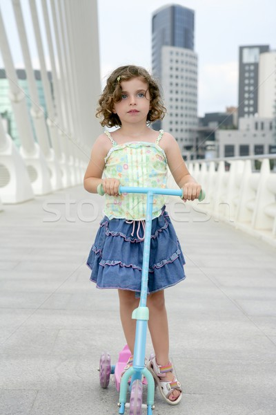 Stock photo: Brunette little girl with scooter in the city