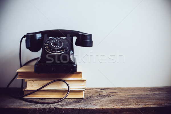 Black vintage rotary phone and books on rustic wooden table, on a white wall background