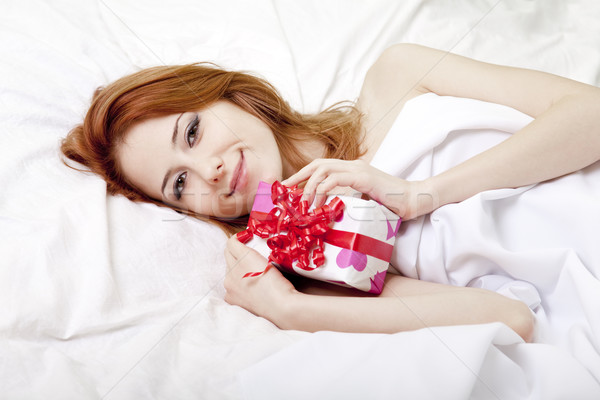 Stock photo: Red-haired girl in bed with gift