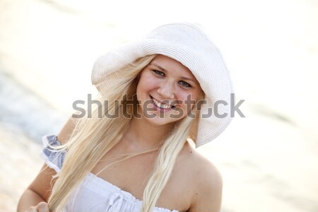 Stock photo: Beautiful young red-haired girl in hat on the beach