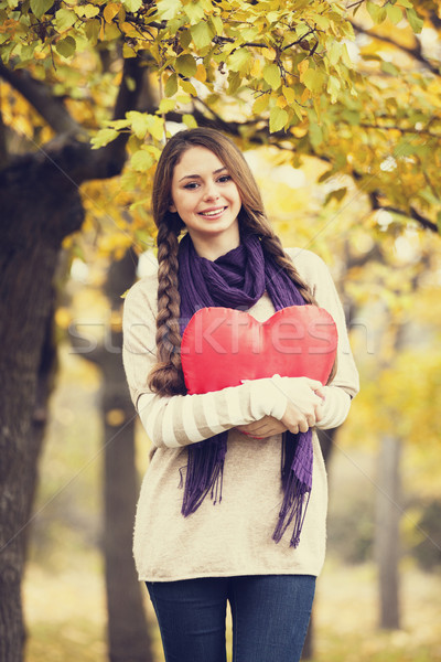 Stock photo: Redhead girl with toy heart at autumn park.