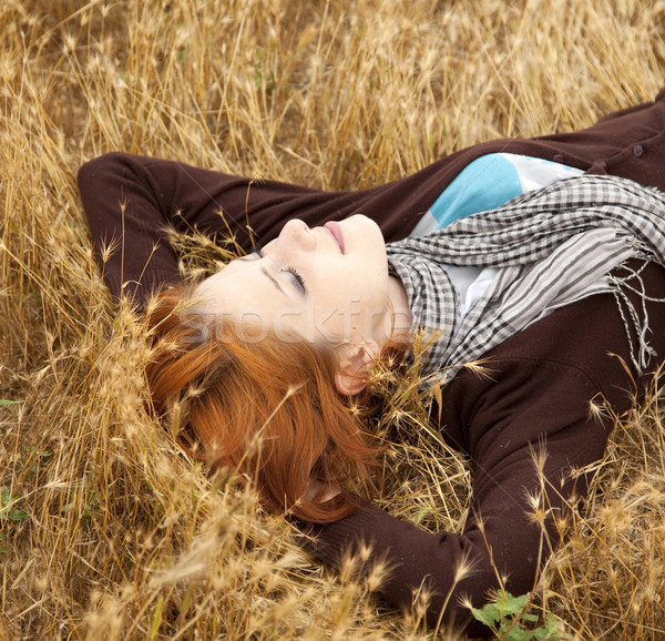 Stock photo: Young beautiful girl lying at yellow autumn field.