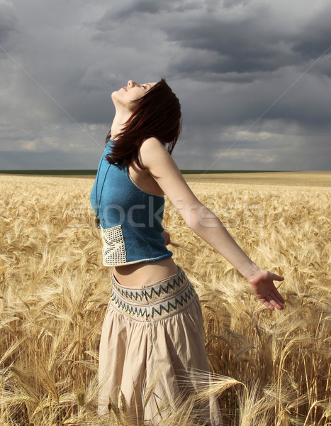 Stock photo: Girl at wheat field in storm day.