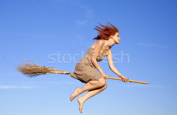 Stock photo: Young red-haired witch on broom flying away