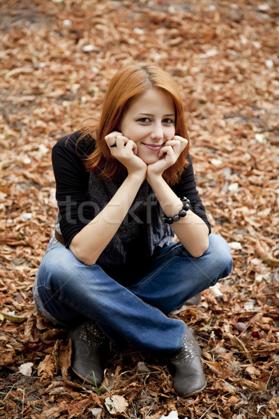 Stock photo: Beautiful red-haired girl in autumn park