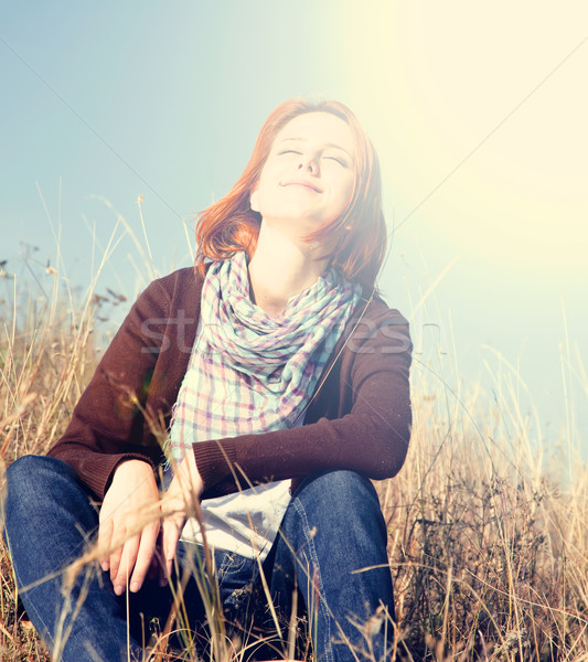 Stock photo: Portrait of happy red-haired girl on autumn grass.