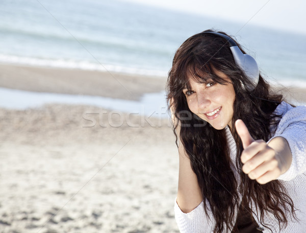 Stock photo: Pretty young woman with headphone on beach