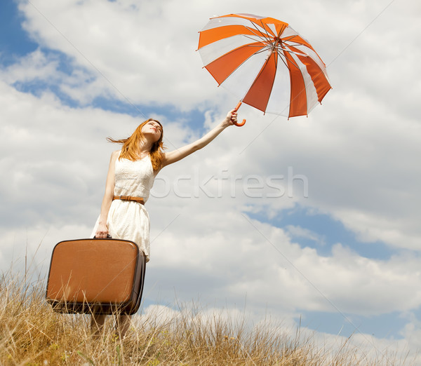 Stock photo: Beautiful redhead girl with umbrella and suitcase at outdoor.