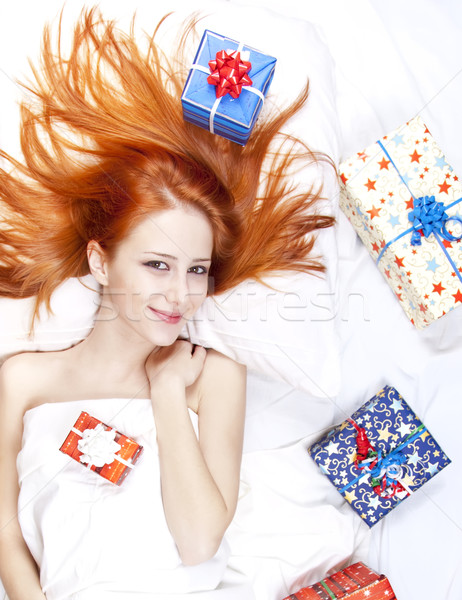 Stock photo: Happy red-haired girl in bed with Christmas gifts.