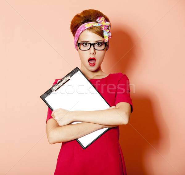 Stock photo: Style redhead girl in glasses and board at pink background.