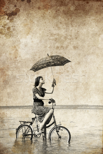 Stock photo: Girl with umbrella on bike. Photo in old image style.