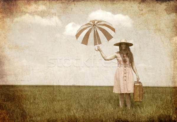 Stock photo: Brunette enchantress with umbrella and suitcase at spring field.