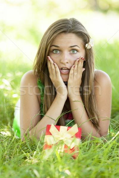 1865621 stock photo surprised beautiful teen girl with gift in the park at green gra JM Waves Mini Bikini Swimsuit