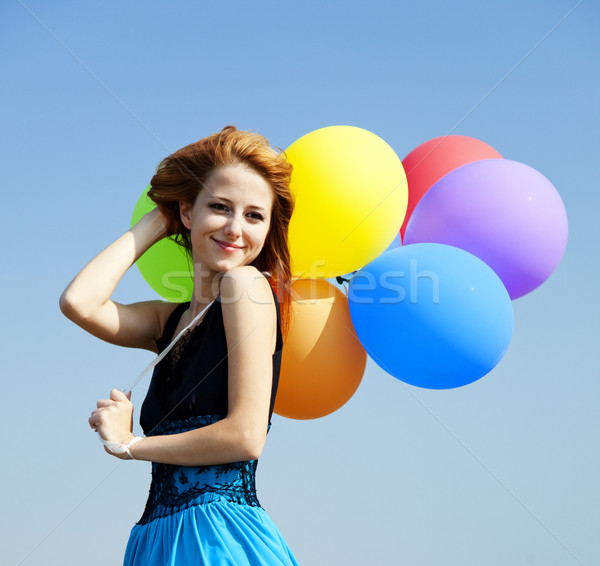 Stock photo: Redhead girl with colour balloons at blue sky background.