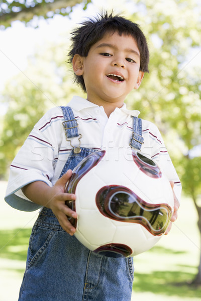 Stock photo: Young boy holding soccer ball outdoors smiling