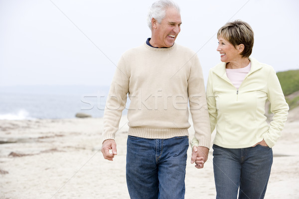 Stock photo: Couple at the beach holding hands and smiling
