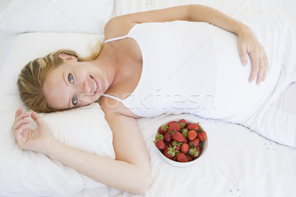 Stock photo: Pregnant woman lying in bed with bowl of strawberries smiling