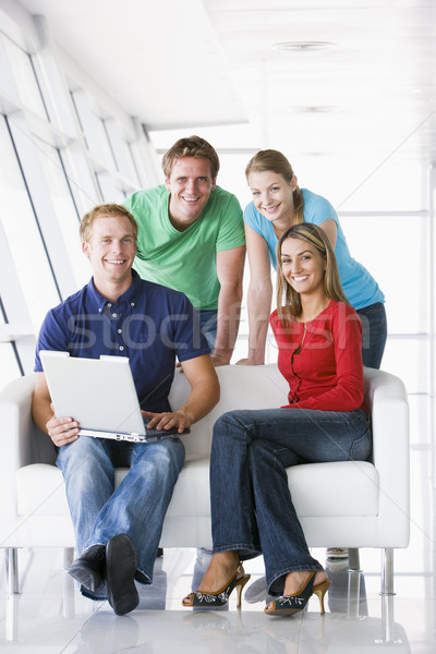 Stock photo: Four people in lobby with laptop smiling