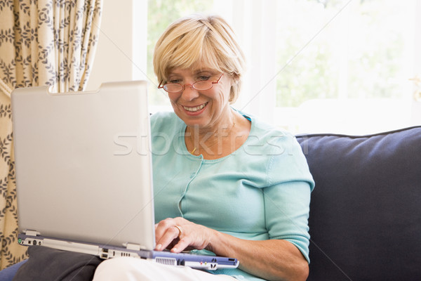 Stock photo: Woman in living room with laptop smiling