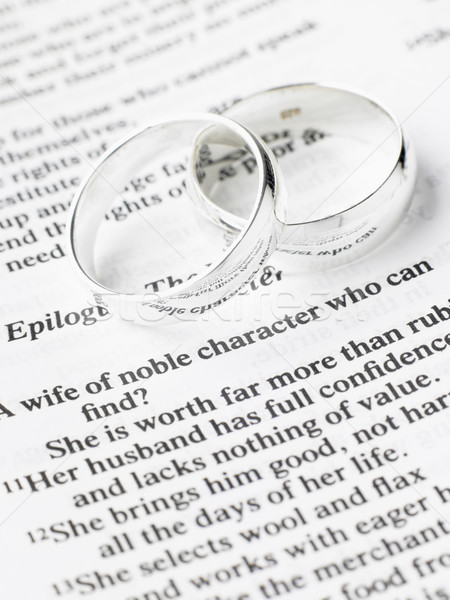 Stock photo Silver Wedding Rings Resting On A Book