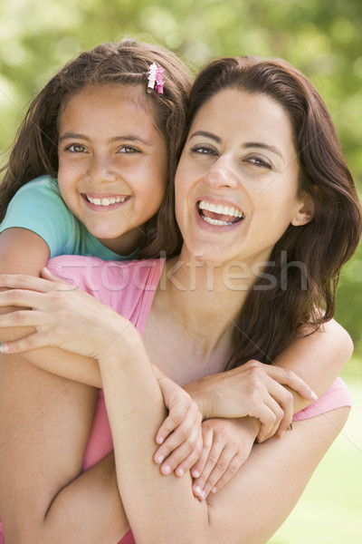 Stock photo: Woman and young girl embracing outdoors smiling