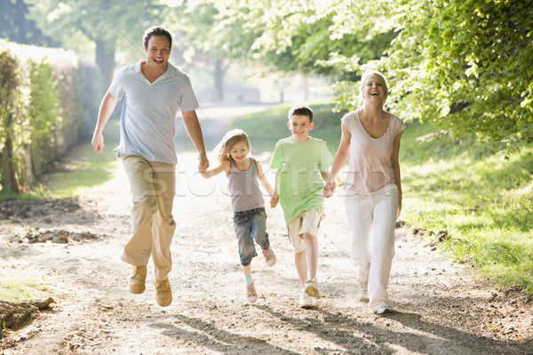 Stock photo: Family running outdoors holding hands and smiling