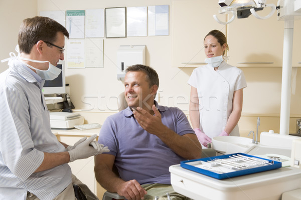Stock photo: Dentist and assistant in exam room with man in chair smiling