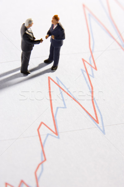 Stock photo: Figurines Of Two Businessmen Shaking Hands On A Line Graph