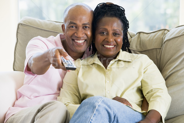 Stock photo: Couple relaxing in living room holding remote control and smilin