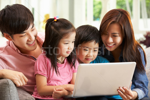 Stock photo: Chinese Family Using Laptop Whilst Relaxing On Sofa At Home
