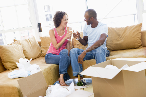 Stock photo: Couple toasting champagne by boxes in new home smiling