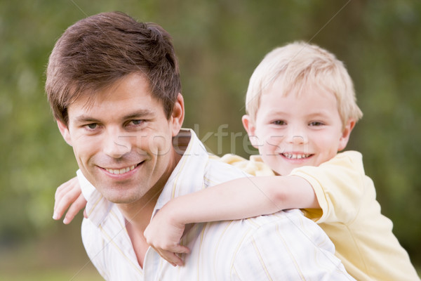 Stock photo: Father holding son outdoors smiling