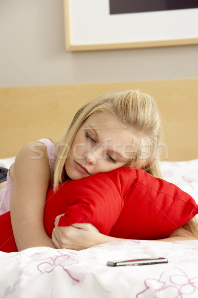 Stock photo: Sad Teenage Girl In Bedroom With Mobile Phone