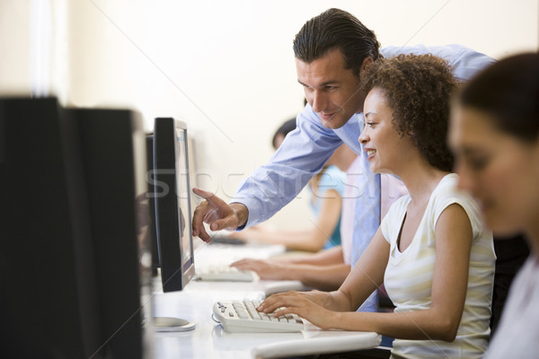 Stock photo: Man assisting woman in computer room