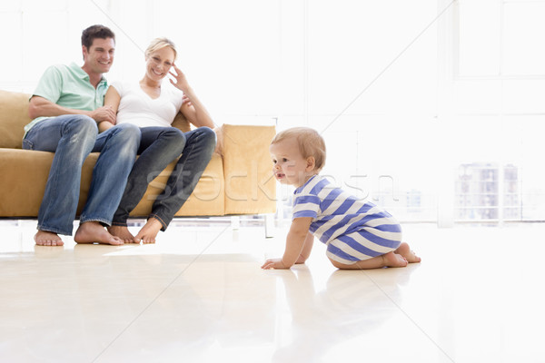 Stock photo: Couple in living room with baby smiling