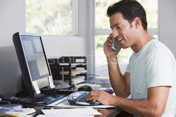 Stock photo: Man in home office on telephone using computer and smiling